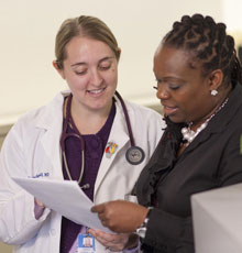 A primary care physician reviewing a patient chart with a co-worker at Tufts Medical Center in Boston.